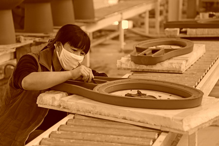 semifinished: LUANNAN COUNTY - JANUARY 5: The women workers repair ceramic semi-finished products in a warehouse, in the ZhongTong Ceramics Co., Ltd. January 5, 2014, Luannan county, Hebei Province, China.