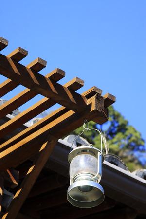 hurricane lamp: Hurricane lamp on the wooden eaves, closeup of photo Stock Photo