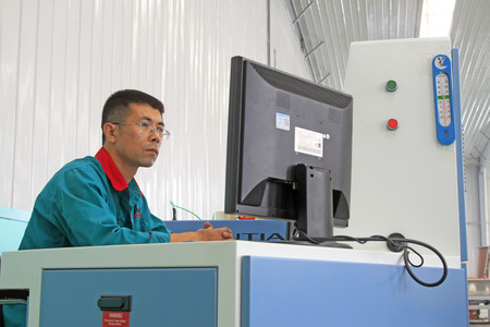 mechanization: LUANNAN COUNTY - AUGUST 23: technicians staring at computer monitors in a production line, on august 23, 2014, Luannan County, Hebei Province, China Editorial