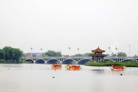 customs and celebrations: LUANNAN COUNTY - AUGUST 5: dragon boat race scene in the river on august 5, 2014, Luannan County, Hebei Province, China. Editorial