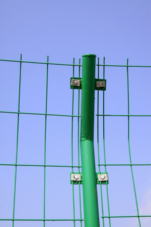 metal fence: green metal fence under the blue sky, closeup of photo
