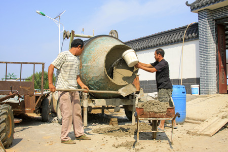 rural development: LUANNAN COUNTY - AUGUST 7: workers busy beside the concrete mixer in rural areas,  on august 7, 2014, Luannan County, Hebei Province, China. Editorial