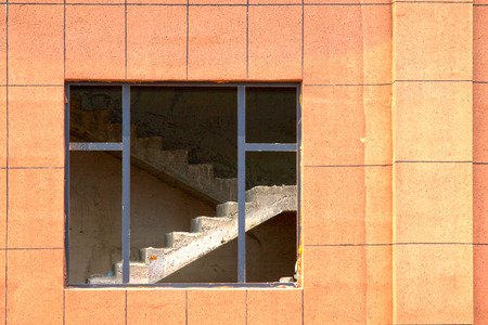 Unfinished building window and stairs, closeup photo