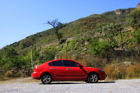 car lots: red car stop in mountain land, closeup photo