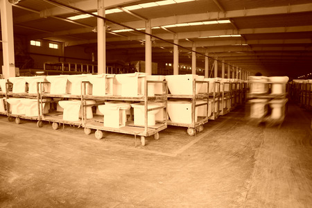 assemblies: LUANNAN COUNTY - JANUARY 5: The worker and ceramic closestool products assemblies in a warehouse, in the ZhongTong Ceramics Co., Ltd. January 5, 2014, Luannan county, Hebei Province, China.