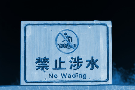 wading: TANGSHAN CITY - NOVEMBER 16: The word prohibit wading on the wood plank in the Tangshan earthquake ruins park, on november 16, 2013, tangshan city, hebei province, China.