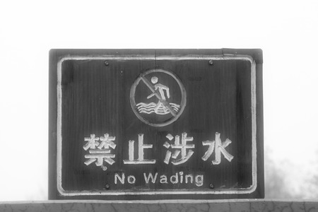 travel features: TANGSHAN CITY - NOVEMBER 16: The word prohibit wading on the wood plank in the Tangshan earthquake ruins park, on november 16, 2013, tangshan city, hebei province, China.
