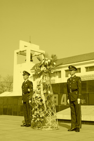 massacre: LUANNAN COUNTY - MARCH 22: Armed police soldiers carrying flower basket, in Pan Dai village massacre memorial building exterior, on March 22, 2014, luannan county, hebei province, China Editorial