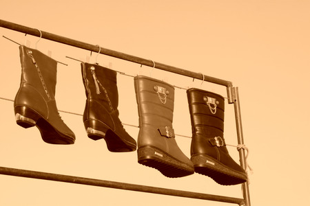 women in boots: women boots hanging in the blue sky, closeup of photo Stock Photo