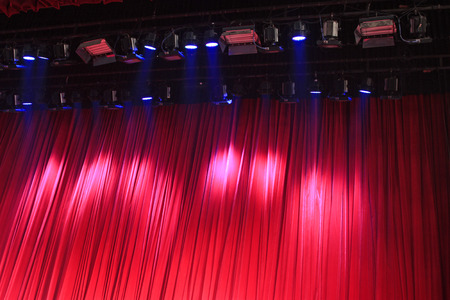 Red curtain and stage lights, closeup of photo Stock Photo
