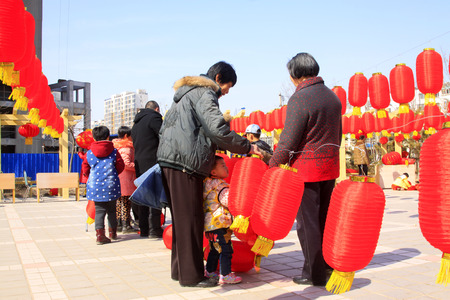 customs and celebrations: LUANNAN COUNTY - MARCH 5: On the Lantern Festival Day, people were busy with hanging red lanterns in a park, March 5, 2015, luannan county, hebei province, China