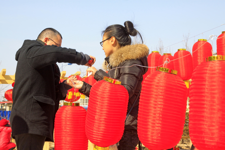 restore ancient ways: LUANNAN COUNTY - MARCH 5: On the Lantern Festival Day, People were busy with hanging red lanterns in a park, March 5, 2015, luannan county, hebei province, China