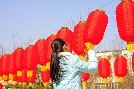 customs and celebrations: LUANNAN COUNTY - MARCH 5: On the Lantern Festival Day, A lady were busy with hanging red lanterns in a park, March 5, 2015, luannan county, hebei province, China