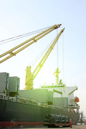 jib: Crane hoisting steel tube on the ship Stock Photo