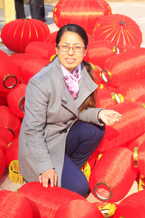 customs and celebrations: LUANNAN COUNTY - MARCH 5: On the Lantern Festival Day, a woman sitting in the middle of red lantern, March 5, 2015, luannan county, hebei province, China Editorial