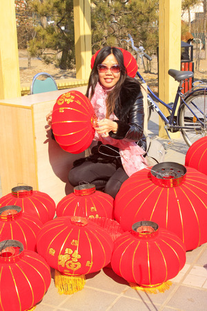customs and celebrations: LUANNAN COUNTY - MARCH 5: On the Lantern Festival Day, A lady taking photo with red lanterns in a park, March 5, 2015, luannan county, hebei province, China Editorial