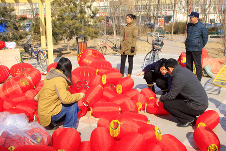 customs and celebrations: LUANNAN COUNTY - MARCH 5: On the Lantern Festival Day, People were busy installing red lanterns in a park, March 5, 2015, luannan county, hebei province, China