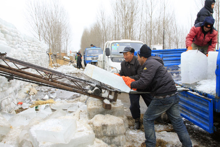 conveyor belt: LUANNAN COUNTY - JANUARY 24: Farmers transportation ice with a conveyor belt in the winter on January 24, 2015, Luannan County, Hebei Province, China
