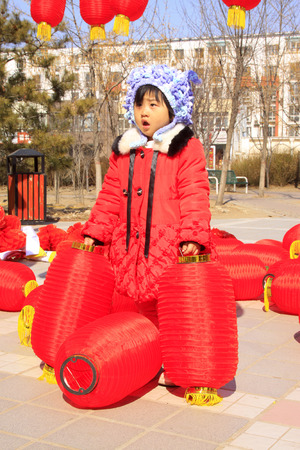 customs and celebrations: LUANNAN COUNTY - MARCH 5: On the Lantern Festival Day, Children playing with red lanterns in a park, March 5, 2015, luannan county, hebei province, China Editorial