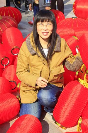 customs and celebrations: LUANNAN COUNTY - MARCH 5: On the Lantern Festival Day, A lady was busy installing red lanterns in a park, March 5, 2015, luannan county, hebei province, China