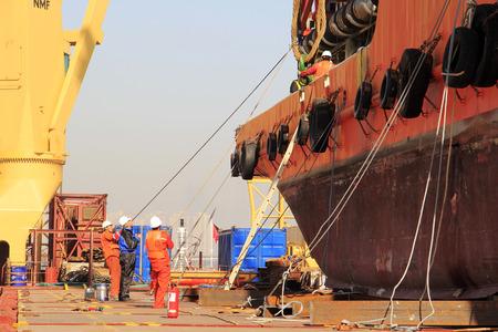 clavados: El puerto de Tianjin - 23 de marzo: los trabajadores fueron atados y fijados buque, el 23 de marzo de 2015, puerto de Tianjin, Tianjin, China.
