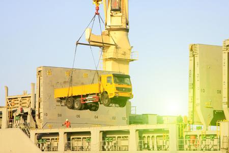 light duty: Heavy trucks are lifting to the cargo ship, closeup of photo