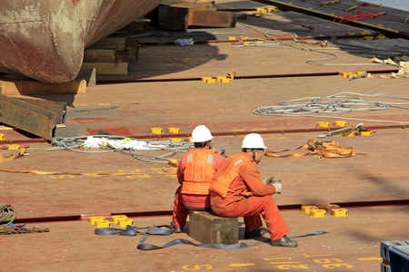 ship deck: workers having rest on the ship deck, closeup of photo