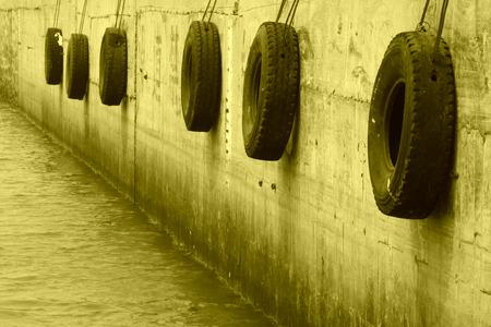 fixed: neumático fijado a la pared en un muelle Foto de archivo