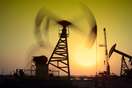 crank: Crank balanced beam pumping unit in Jidong oilfield sunset scenery, Hebei Province, China Stock Photo