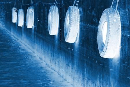clavados: neumático fijado a la pared en un muelle Foto de archivo