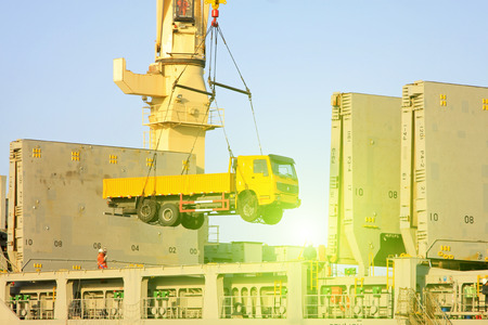 traction: Heavy trucks are lifting to the cargo ship, closeup of photo