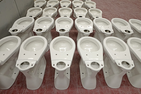 implementing: Ceramic toilet parts in a factory, closeup of photo