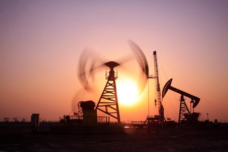 crank: Crank balanced beam pumping unit in Jidong oilfield sunset scenery, Hebei Province, China Editorial