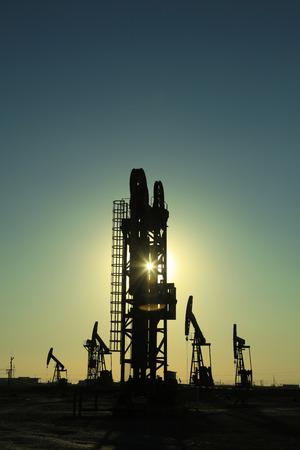 yacimiento petrolero: unidad de bombeo tipo torre bajo el sol poniente en un campo petrolífero