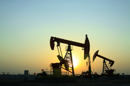 crank: Crank balanced beam pumping unit in Jidong oilfield sunset scenery, Hebei Province, China Editorial