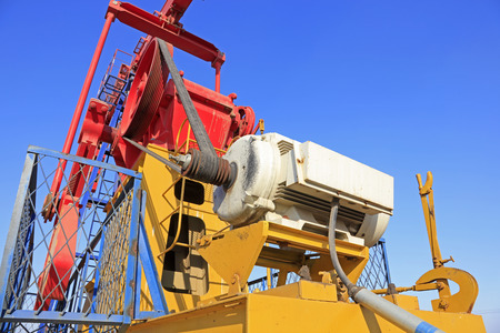 oilfield: motor on pumping unit under blue sky in oilfield