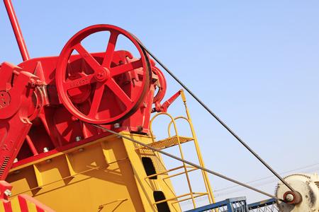 yacimiento petrolero: ruedas de la maquinaria de petróleo bajo el cielo azul en el campo petrolífero Editorial