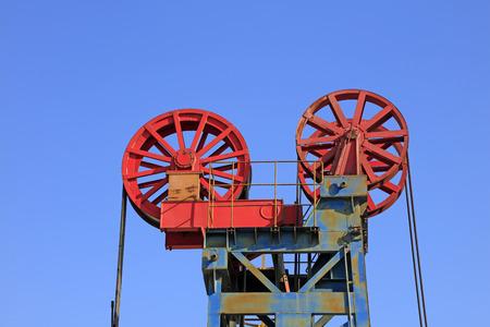 yacimiento petrolero: piezas de maquinaria de petróleo bajo el cielo azul en el campo petrolífero Foto de archivo