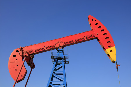 oilfield: pumping unit walking beam under blue sky in oilfield