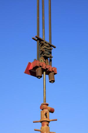 yacimiento petrolero: aceite de dispositivo mecánico bajo el cielo azul en el campo petrolífero Foto de archivo