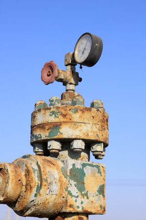 gage: Oil pipeline control handwheel and pressure gage, closeup of photo