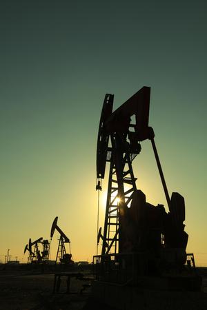 yacimiento petrolero: Haz de la unidad de bombeo equilibrada bajo el sol poniente en el campo petrolífero Foto de archivo