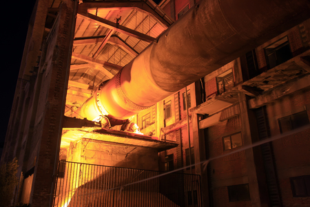 kiln: idle cement plant rotary kiln machinery at night, closeup of photo