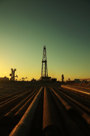 derrick: Oil drilling derrick and pipelines in oilfield