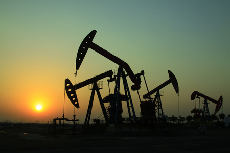 crank: Crank balanced beam pumping unit in oilfield sunset scenery, Hebei Province, China Stock Photo