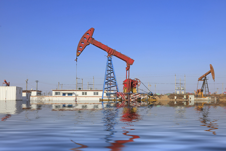 oilfield: pumping unit and reflection in oilfield Editorial
