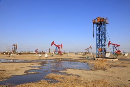 yacimiento petrolero: tower type pumping unit under blue sky in oilfield Foto de archivo