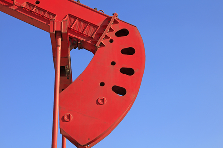 oilfield: pumping unit mechanical components under blue sky in oilfield