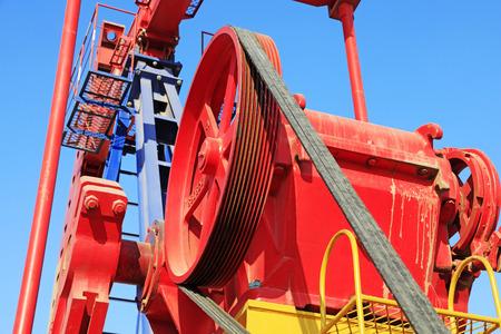 yacimiento petrolero: wheels on petroleum machinery under blue sky in oilfield Editorial