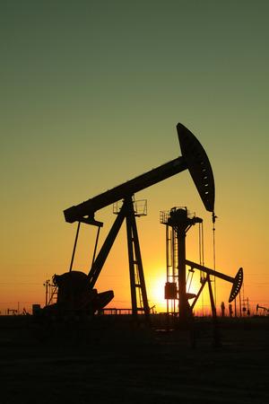 yacimiento petrolero: Haz de la unidad de bombeo equilibrada bajo el sol poniente en el campo petrolífero Editorial